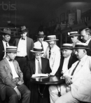 """How it Started"" Principals of Scopes trial grouped around table in Robinson's Drug Store (specially posed) Seated – H.E.Hicks, attorney; John T. Scopes; Walter White, Rhea County superintendent of schools; and County Judge J.G. McKenzie; Standing – B.M. Wilber, justice of the peace; W.C. Haggard, an attorney; W.E. Morgan; Dr George W.Rappelyea, chemical engineer, who initiated prosecution of his friend to test the law; S.K. Hicks, attorney and F.E. Robinson, chairman, Rhea County Board of Education"