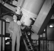 Dr. Harold Spencer standing next to a giant reflecting telescope at Woolich Observatory, London